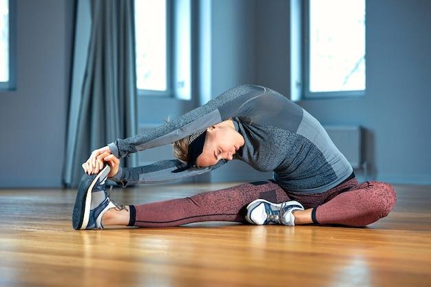 Belle jeune femme en tenue de sport faisant des étirements alors qu'il était assis sur le sol en face de la fenêtre au gymnase