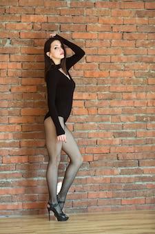 Belle jeune femme en tenue de sport noire près d'un mur de briques