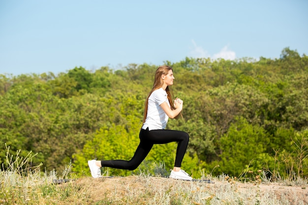 Belle jeune femme en tenue de sport en plein air sur la prairie verte