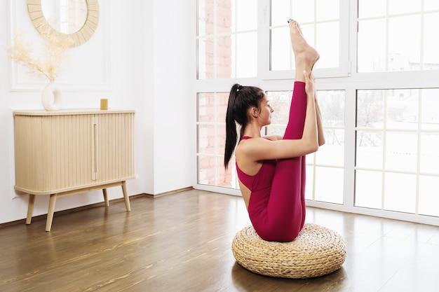 Belle jeune femme en tenue de sport pratiquant le yoga est assise sur le sol en faisant de l'urdhva mukha paschimottanasana exercice dans la salle près de la grande fenêtre