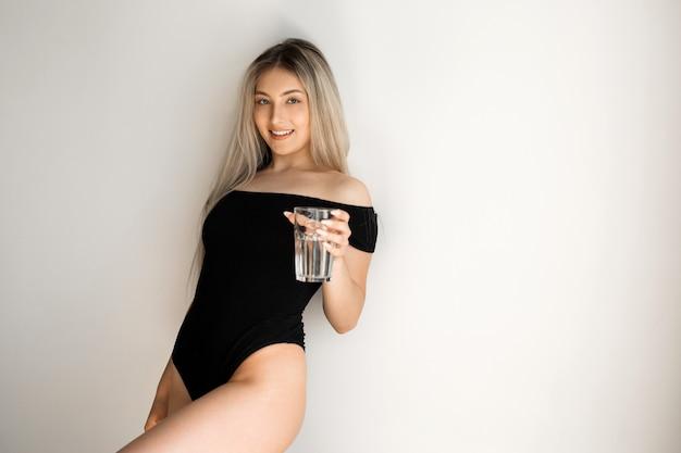 Belle jeune femme en tenue de sport avec un verre d'eau