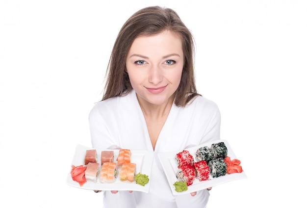 Belle jeune femme tient une assiette avec des sushis.