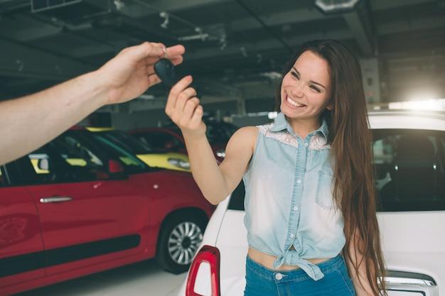 Belle jeune femme tient une clé dans le concessionnaire automobile