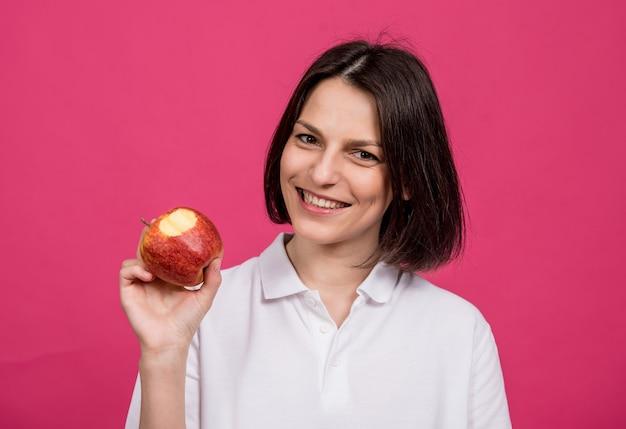 Belle jeune femme tient une grosse pomme dans sa main