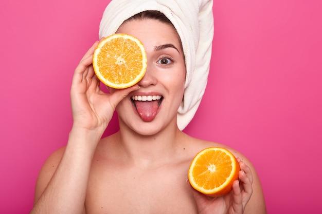 Belle jeune femme tient la moitié d'orange dans sa main et contre l'oeil avec une autre partie de fruit. jolie femme avec une serviette sur la tête se dresse sur le rose. procédure quotidienne et concept de beauté.