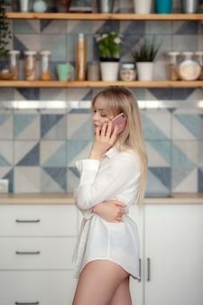 Une belle jeune femme tient un téléphone portable et appelle un ami, discute de recettes et de sourires, debout près d'une table sur laquelle se trouvent des fruits et des légumes avec une variété d'appareils de cuisson au milieu d'un style élégant