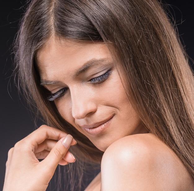 Belle jeune femme torse nue en gardant les yeux fermés.