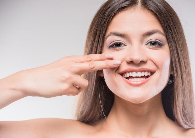 Belle jeune femme touchant la peau ou appliquant une crème.