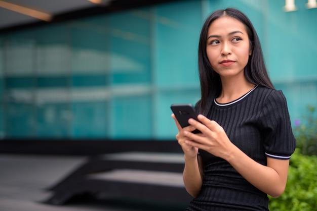 Belle jeune femme touriste asiatique pensant tout en utilisant le téléphone au centre commercial à l'extérieur