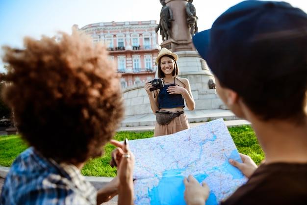 Belle jeune femme touriste souriante, prenant une photo de ses amis.