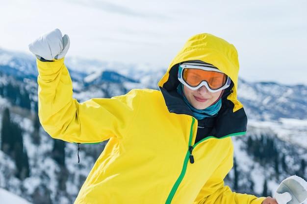Belle jeune femme touriste en veste jaune masque de lunettes de ski et mitaines blanches sur les montagnes