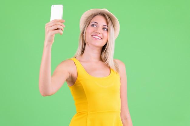 Belle jeune femme touristique aux cheveux blonds sur clé chroma sur vert