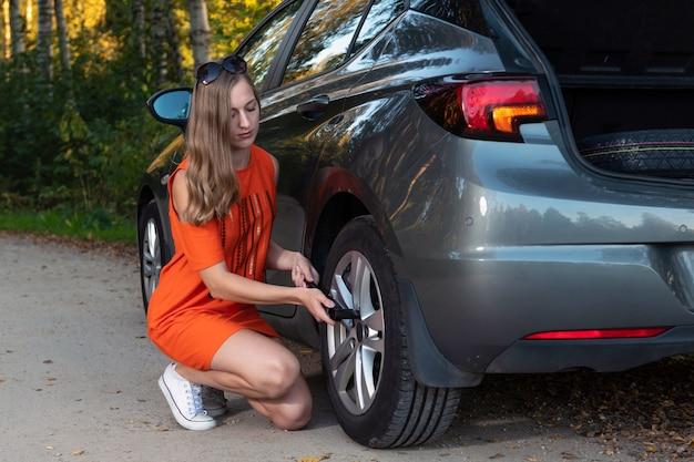 Belle jeune femme en train de changer une roue endommagée et de la réparer