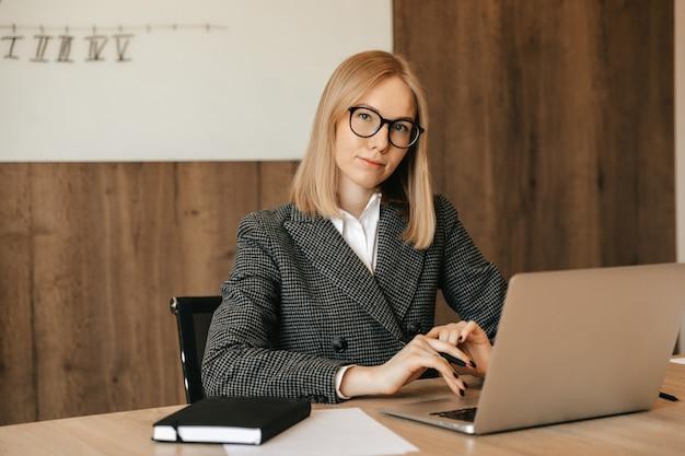Belle jeune femme travaillant à l'aide d'un ordinateur portable, concentrée et sérieuse, bonne employée de bureau responsable.