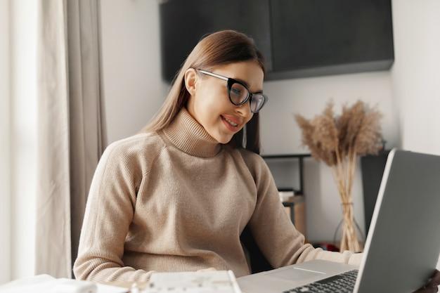 Belle jeune femme travaillant sur un ordinateur portable alors qu'il était assis dans le salon, buvant du café. bureau à domicile pendant la quarantaine coronavirus ou covid-19.