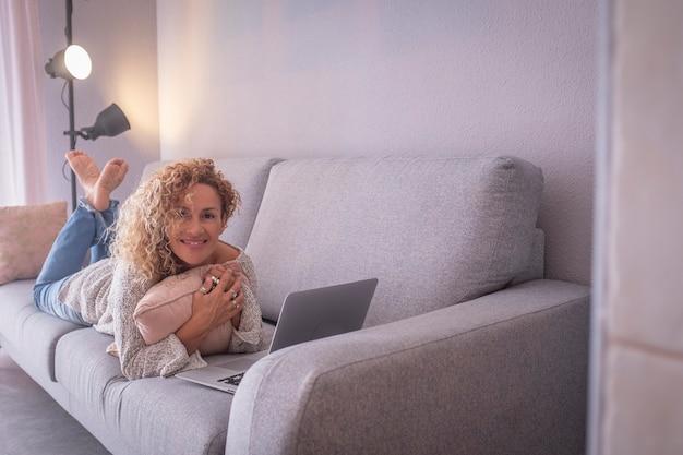 Belle jeune femme travaillant en se trouvant devant un ordinateur portable sur un canapé. portrait d'une femme d'affaires heureuse travaillant à domicile. femme passant du temps libre à l'aide d'un ordinateur portable sur un canapé dans le salon