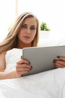 Belle jeune femme travaillant avec tablette restant au lit tôt le matin