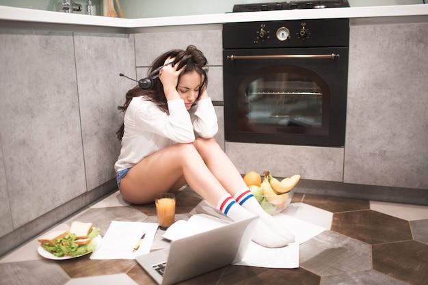 Une belle jeune femme travaille toute la nuit dans la cuisine de sa maison elle est très fatiguée.