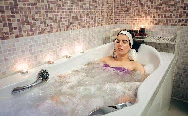 Belle jeune femme avec turban allongée dans la baignoire faisant un traitement d'hydrothérapie. concept de santé et de beauté.