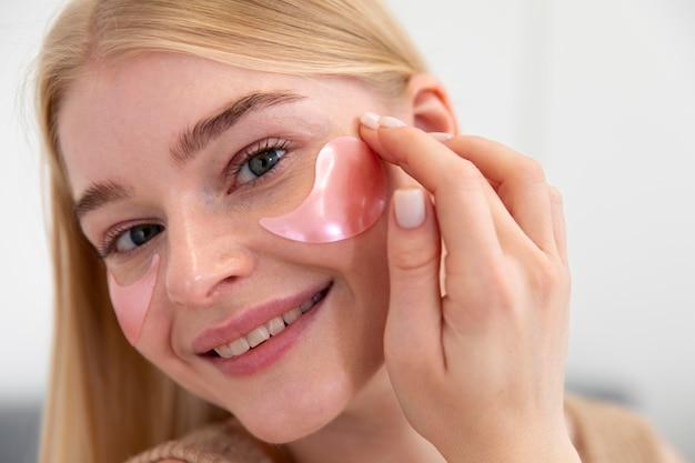 Belle jeune femme utilisant un produit de soin du visage