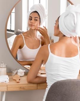 Belle jeune femme utilisant des produits et regardant dans le miroir