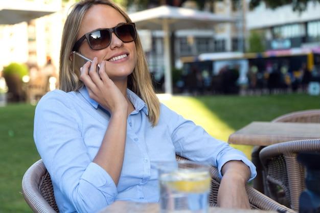 Belle jeune femme utilisant son téléphone mobile dans un restaurant ter