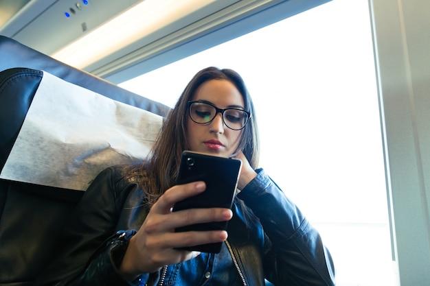 Belle jeune femme utilisant son téléphone mobile dans la rue.