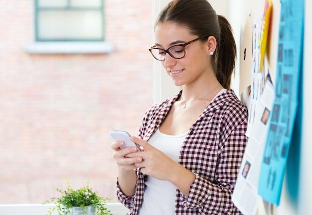 Belle jeune femme utilisant son téléphone portable au bureau.