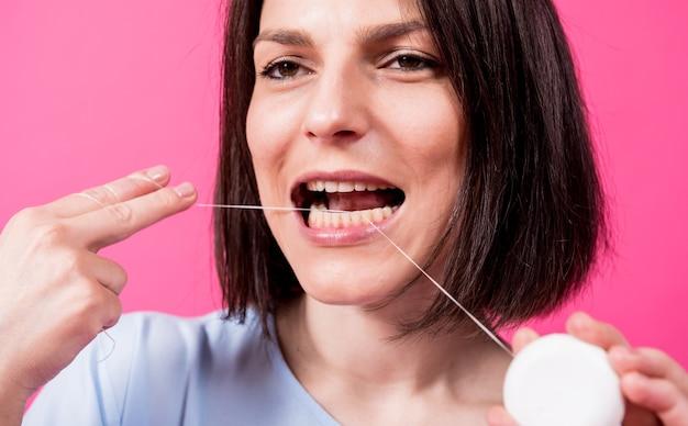 Belle jeune femme utilise du fil dentaire sur fond rose