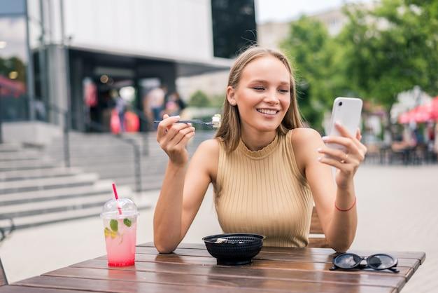 Belle jeune femme utilise le téléphone tout en mangeant de la salade au café en plein air