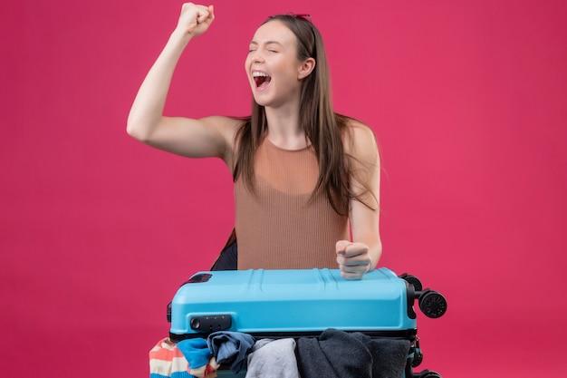 Belle jeune femme avec valise de voyage levant le poing après une victoire sortie et heureux sur mur rose