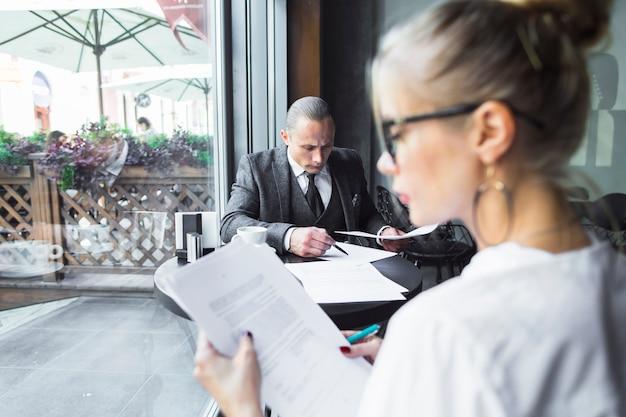 Belle jeune femme vérifiant les documents dans le caf�