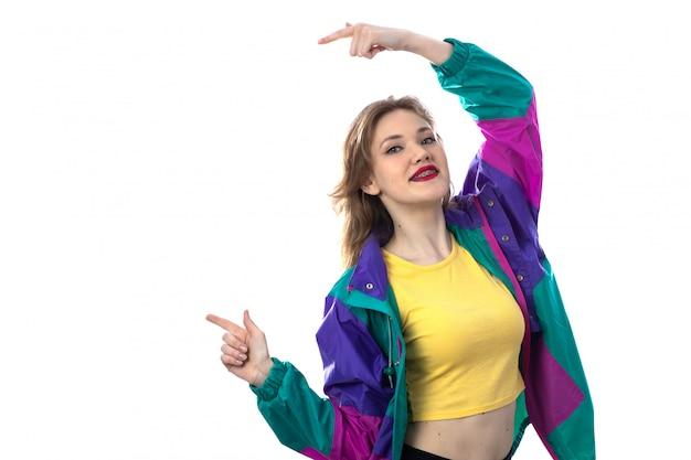 Belle jeune femme en veste colorée pointant