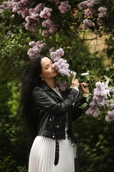 Belle jeune femme en veste de cuir appréciant l'odeur du lilas fleuri au printemps