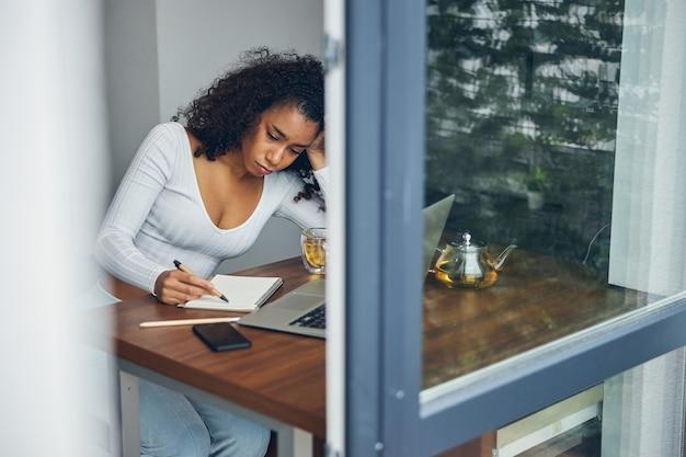 Belle jeune femme en vêtements décontractés assise et l'air triste tout en travaillant en ligne sur un ordinateur portable