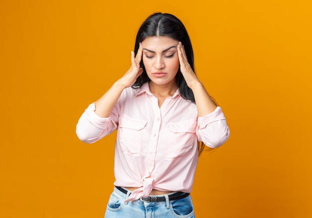 Belle jeune femme en vêtements décontractés ayant l'air malade de toucher ses tempes souffrant de maux de tête debout sur un mur orange