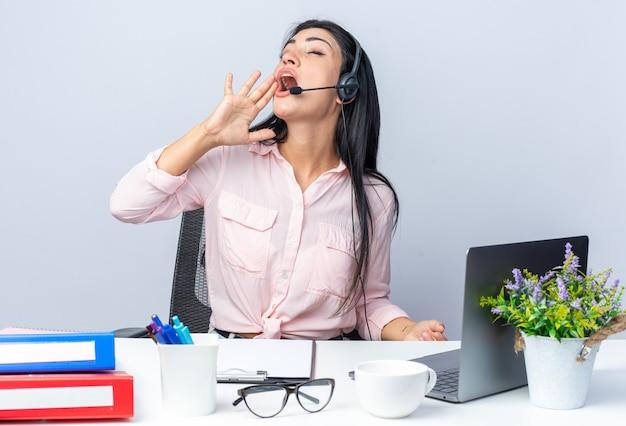Belle jeune femme en vêtements décontractés avec un casque et un microphone criant fort avec la main sur la bouche assise à la table avec un ordinateur portable sur un mur blanc travaillant au bureau