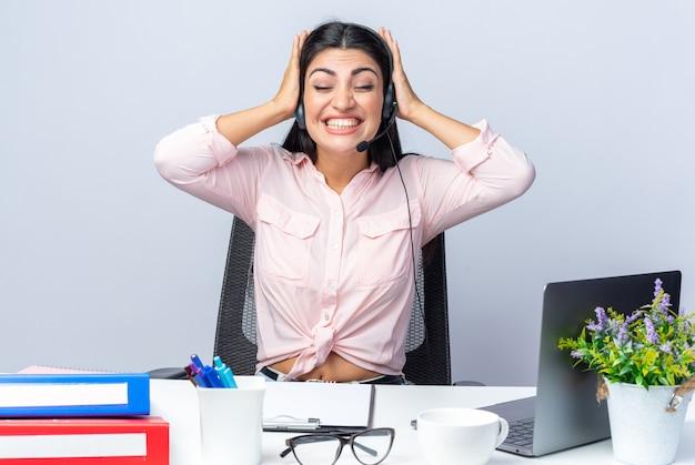 Belle jeune femme en vêtements décontractés avec casque et microphone heureuse et excitée tenant les mains sur la tête assise à la table avec un ordinateur portable sur blanc