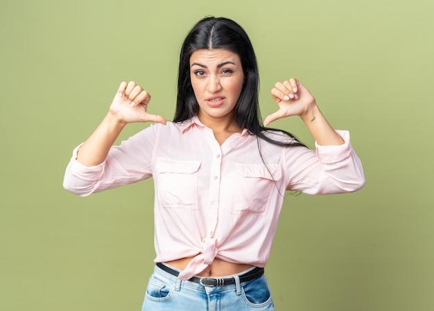 Belle jeune femme en vêtements décontractés confus se pointant sur elle-même debout sur un mur vert