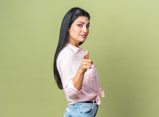 Belle jeune femme en vêtements décontractés avec une expression confiante pointant avec l'index debout sur un mur vert