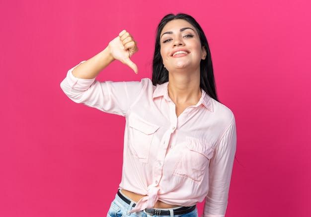 Belle jeune femme en vêtements décontractés, heureuse et positive souriante montrant joyeusement les pouces vers le bas, debout sur le mur rose