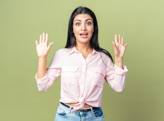Belle jeune femme en vêtements décontractés heureuse et surprise avec les bras levés debout sur un mur vert