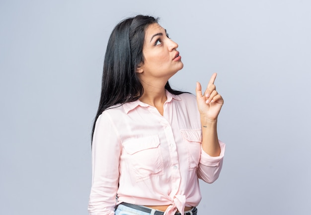 Belle jeune femme en vêtements décontractés levant intriguée pointant avec l'index debout sur un mur blanc