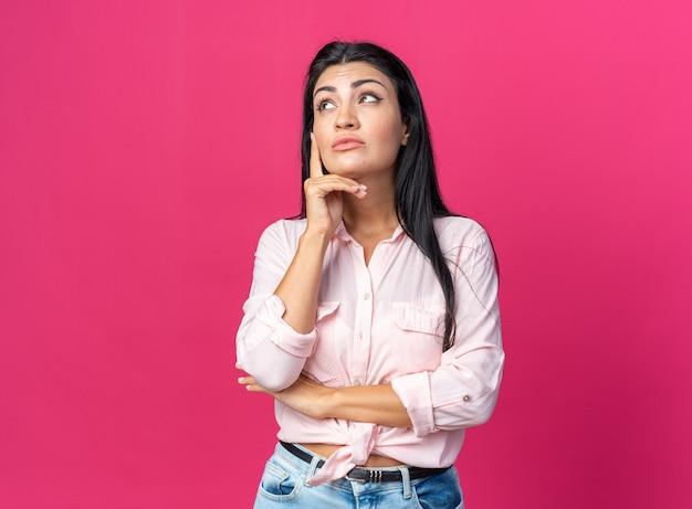 Belle jeune femme en vêtements décontractés levant perplexe avec la main sur son menton