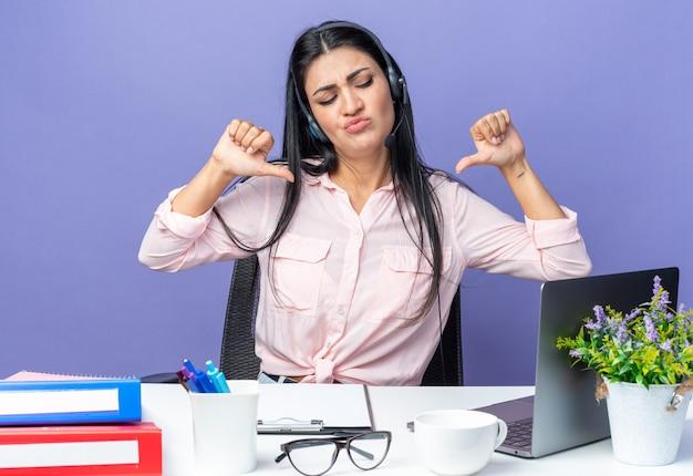 Belle jeune femme en vêtements décontractés portant un casque avec microphone à la confiance en se pointant sur elle-même assise à la table avec un ordinateur portable sur bleu