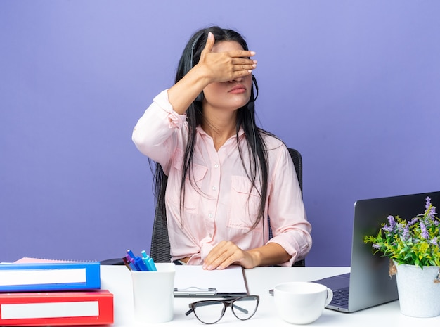 Belle jeune femme en vêtements décontractés portant un casque avec microphone couvrant les yeux avec la main assise à la table avec un ordinateur portable sur un mur bleu travaillant au bureau
