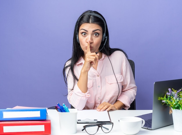 Belle jeune femme en vêtements décontractés portant un casque avec microphone faisant un geste de silence avec le doigt sur les lèvres inquiet assis à la table avec un ordinateur portable sur un mur bleu travaillant au bureau
