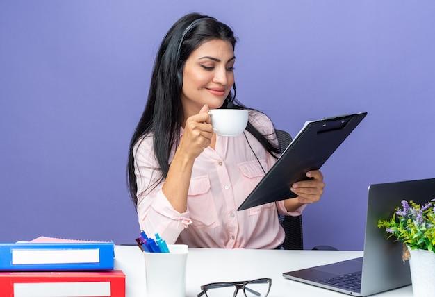 Belle jeune femme en vêtements décontractés portant un casque avec microphone tenant un presse-papiers buvant du café heureux et confiant assis à la table avec un ordinateur portable sur un mur bleu travaillant au bureau