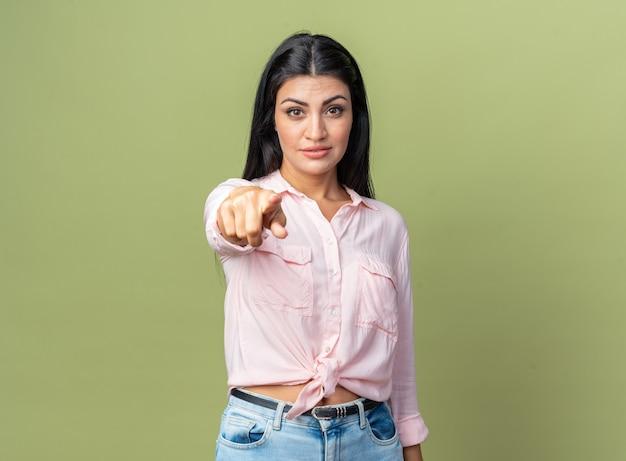 Belle jeune femme en vêtements décontractés à la recherche de confiance en pointant avec l'index debout sur le mur vert