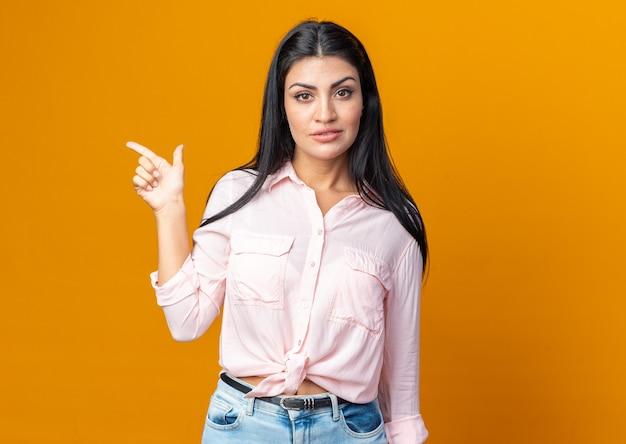 Belle jeune femme en vêtements décontractés regardant à l'avant avec une expression confiante pointant avec l'index sur le côté debout sur le mur orange